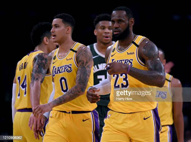 LeBron James and Kyle Kuzma of the Los Angeles Lakers react after a James score, in front of Giannis Antetokounmpo of the Milwaukee Bucks during a...