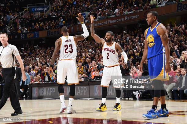 LeBron James and Kyrie Irving of the Cleveland Cavaliers highfive in Game Three of the 2017 NBA Finals on June 7 2017 at Quicken Loans Arena in...