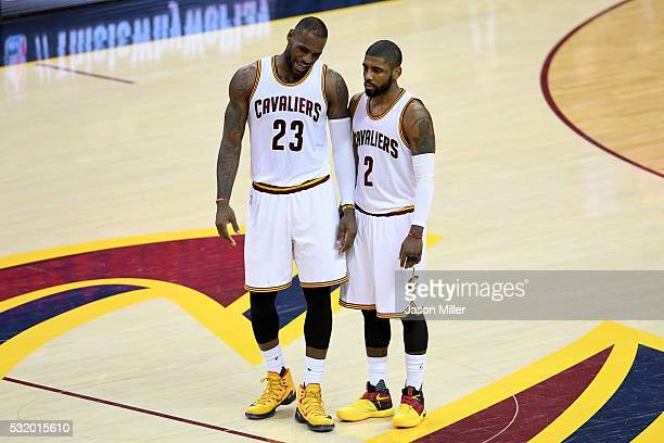LeBron James and Kyrie Irving of the Cleveland Cavaliers talk at mid court in the first half against the Toronto Raptors in game one of the Eastern...