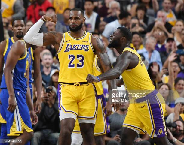 LeBron James and Lance Stephenson of the Los Angeles Lakers celebrate after James made a shot against the Golden State Warriors and was fouled during...