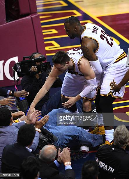 LeBron James and Matthew Dellavedova of the Cleveland Cavaliers help a cameraman up after a collision in the second quarter against the Toronto...