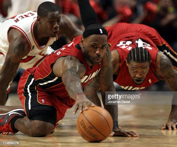 LeBron James and Udonis Haslem of the Miami Heat dive for a loose ball against Ronnie Brewer of the Chicago Bulls in Game Five of the Eastern...