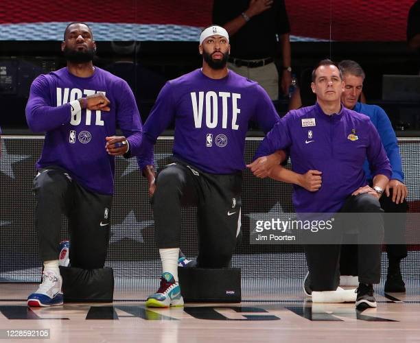 LeBron James Anthony Davis and Head Coach Frank Vogel of the Los Angeles Lakers during the national anthem against the Denver Nuggets in Game one of...