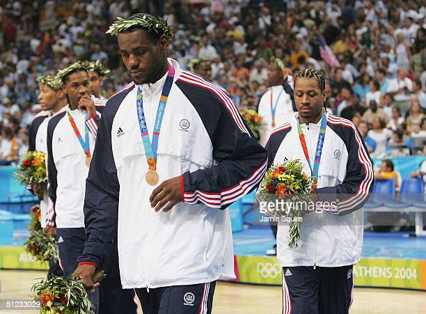 LeBron James Carmelo Anthony and Allen Iverson of the United States walk off the court after they receive the bronze medal for men's basketball...