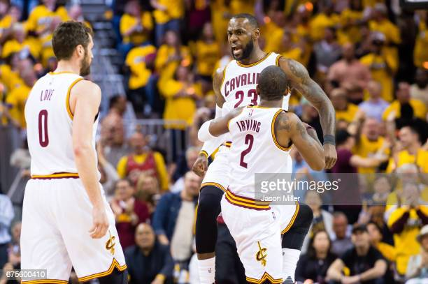 LeBron James celebrates with Kyrie Irving and Kevin Love of the Cleveland Cavaliers after scoring during the first half of Game One of the NBA...