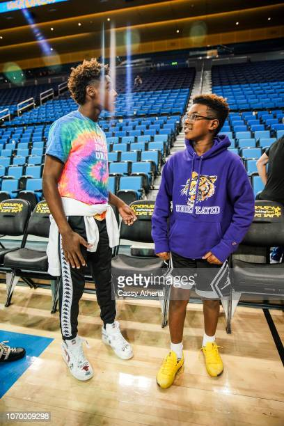LeBron James Jr and Bryce James hang out court side after a game against the UCLA Bruins and the Presbyterian Blue Hose at Pauley Pavilion on...