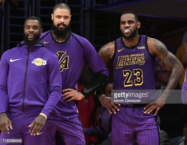 LeBron James of and Tyson Chandler and Lance Stephenson of the Los Angeles Lakers follow the game from the bench at the end of the basketball game...