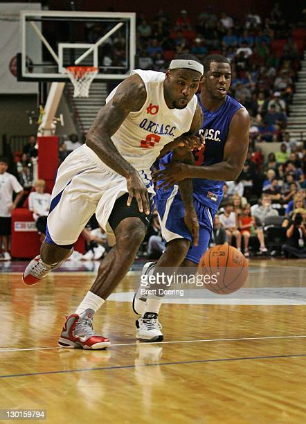 LeBron James of Team White drives up court on Chris Paul of Team Blue during the USFleet Tracking Basketball Invitational charity basketball game...