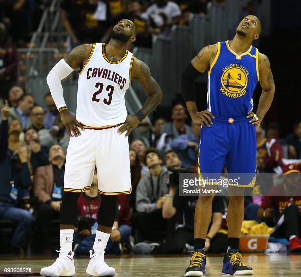 LeBron James of the Cleveland Cavaliers and David West of the Golden State Warriors look up at the scoreboard during the first half of Game 3 of the...