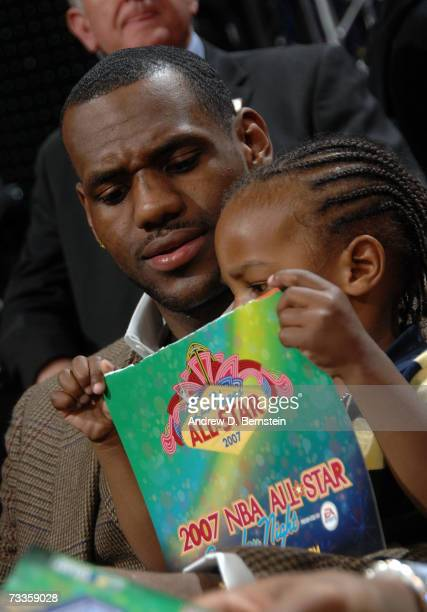 LeBron James of the Cleveland Cavaliers and his son look at the program for the 2007 NBA All-Star Weekend before the start of the Sprite Slam Dunk...