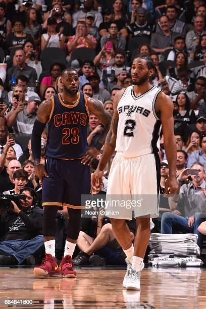 LeBron James of the Cleveland Cavaliers and Kawhi Leonard of the San Antonio Spurs stand on the court during a game on March 27 2017 at the ATT...