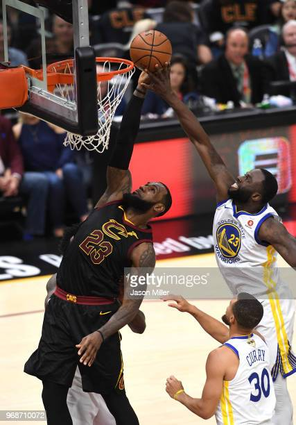 LeBron James of the Cleveland Cavaliers attempts a layup defended by Draymond Green of the Golden State Warriors in the first half during Game Three...