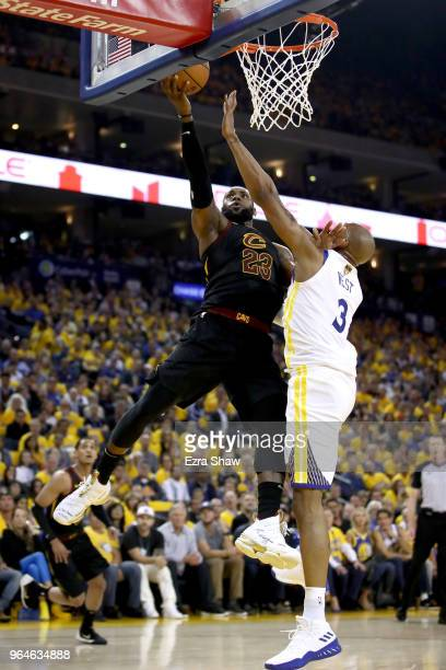 LeBron James of the Cleveland Cavaliers attempts a layup over David West of the Golden State Warriors in Game 1 of the 2018 NBA Finals at ORACLE...