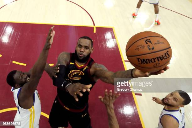 LeBron James of the Cleveland Cavaliers attempts a layup over Draymond Green and Stephen Curry of the Golden State Warriors in the first half during...