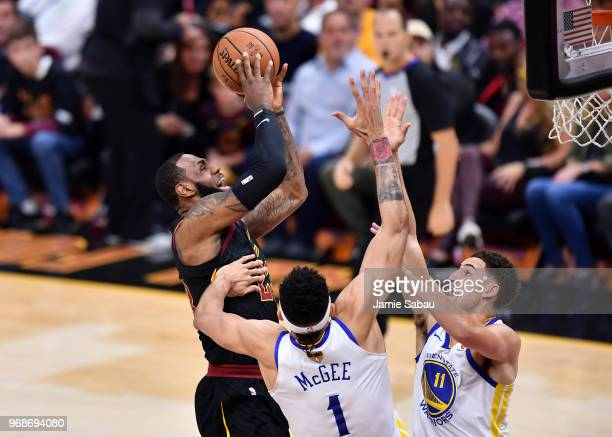 LeBron James of the Cleveland Cavaliers attempts a layup over JaVale McGee and Klay Thompson of the Golden State Warriors in the first quarter during...