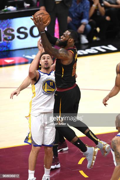 LeBron James of the Cleveland Cavaliers attempts a layup over Klay Thompson of the Golden State Warriors in the first quarter during Game Three of...