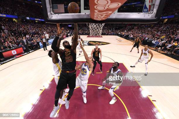 LeBron James of the Cleveland Cavaliers attempts a layup over Stephen Curry and Jordan Bell of the Golden State Warriors in the first half during...