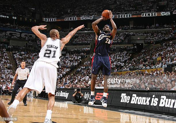 LeBron James of the Cleveland Cavaliers attempts a shot against Tim Duncan of the San Antonio Spurs in Game One of the NBA Finals at the AT&T Center...