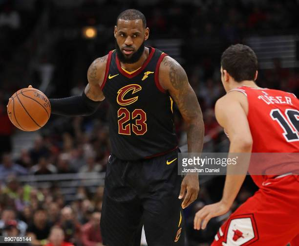 LeBron James of the Cleveland Cavaliers brings the ball up the court against Paul Zipser of the Chicago Bulls at the United Center on December 4 2017...