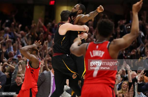 LeBron James of the Cleveland Cavaliers celebrates his game winning shot with Kevin Love behind Kyle Lowry of the Toronto Raptors during Game Three...