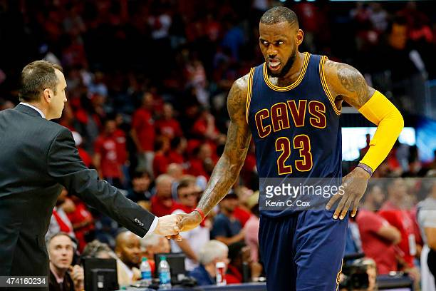 LeBron James of the Cleveland Cavaliers celebrates their 97 to 89 win over the Atlanta Hawks with head coach David Blatt during Game One of the...