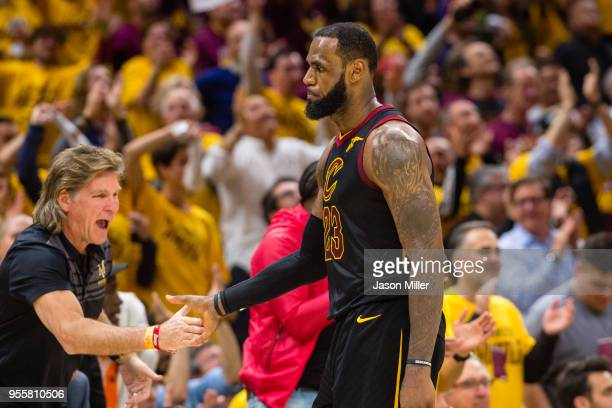 LeBron James of the Cleveland Cavaliers celebrates with a fan after scoring against the Toronto Raptors during the second half of Game 4 of the...