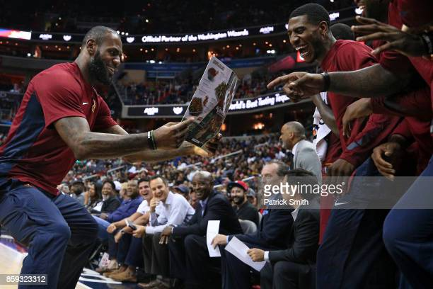 LeBron James of the Cleveland Cavaliers celebrates with teammates as he looks at a Greene Turtle restaurant menu after teammate Jeff Green dunked in...