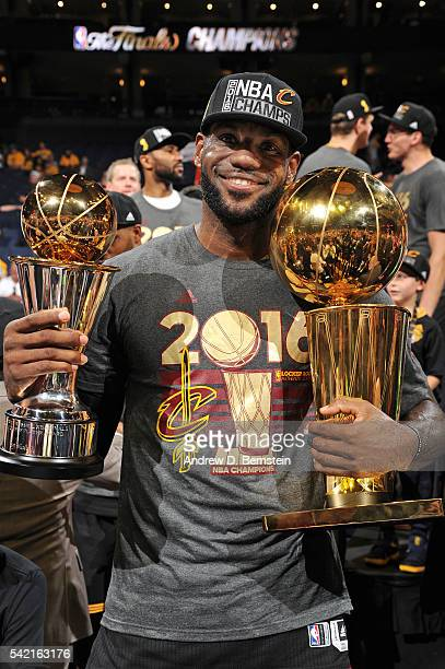 LeBron James of the Cleveland Cavaliers celebrates with the Bill Russell NBA Finals Most Valuable Player Award and the Larry O'Brien NBA Championship...