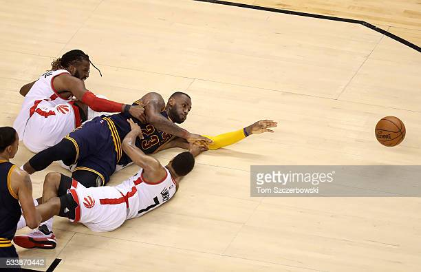 LeBron James of the Cleveland Cavaliers competes for a loose ball late in the game against DeMarre Carroll and Kyle Lowry of the Toronto Raptors in...