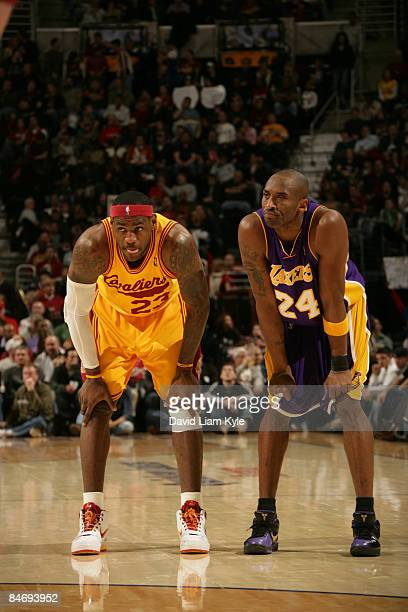 LeBron James of the Cleveland Cavaliers crouches besides Kobe Bryant of the Los Angeles Lakers during a break in the action at The Quicken Loans...