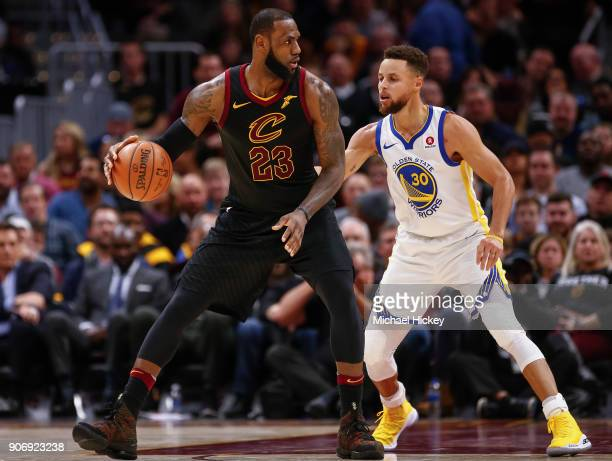 LeBron James of the Cleveland Cavaliers dribbles the ball against Stephen Curry of the Golden State Warriors at Quicken Loans Arena on January 15...