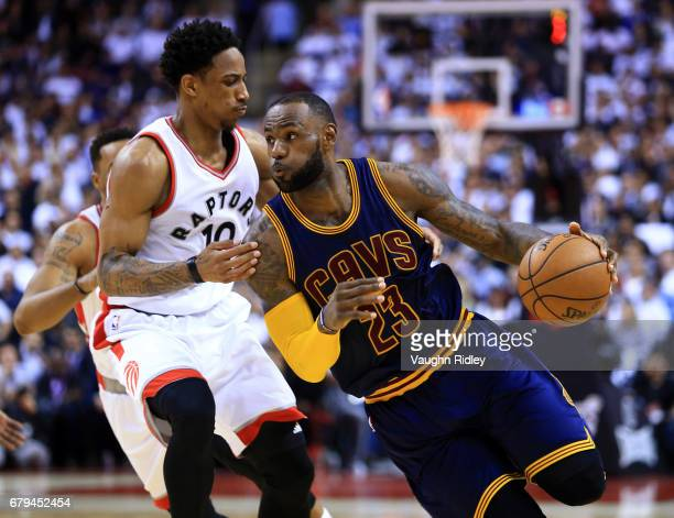 Lebron James of the Cleveland Cavaliers dribbles the ball as DeMar DeRozan of the Toronto Raptors defends in the second half of Game Three of the...