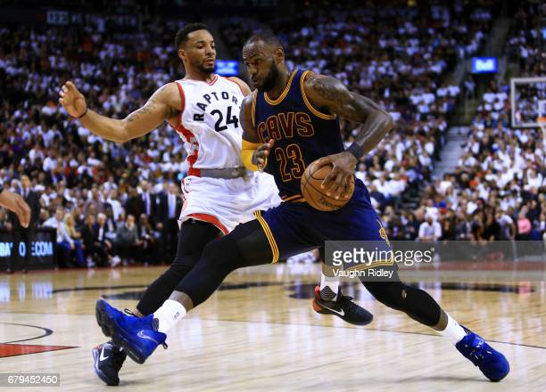 Lebron James of the Cleveland Cavaliers dribbles the ball as Norman Powell of the Toronto Raptors defends in the second half of Game Three of the...