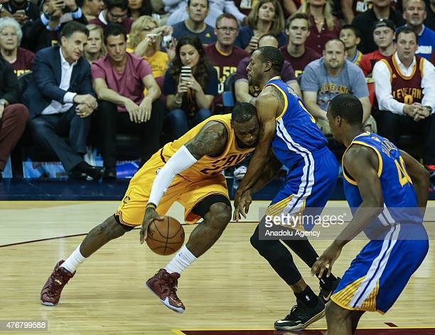 LeBron James of the Cleveland Cavaliers drives against Andre Iguodala and Harrison Barnes of the Golden State Warriors during Game Four of the 2015...