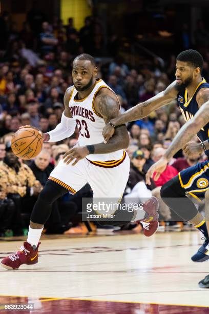 LeBron James of the Cleveland Cavaliers drives around Paul George of the Indiana Pacers during the first overtime period at Quicken Loans Arena on...