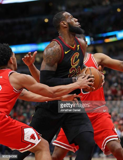 LeBron James of the Cleveland Cavaliers drives between Cameron Payne and Cristiano Felicio of the Chicago Bulls at the United Center on March 17 2018...