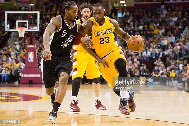 LeBron James of the Cleveland Cavaliers drives past Kawhi Leonard of the San Antonio Spurs during the first half at Quicken Loans Arena on January 30...