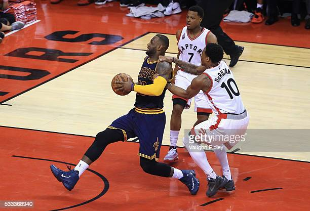 LeBron James of the Cleveland Cavaliers drives to the basket against Kyle Lowry of the Toronto Raptors and DeMar DeRozan during the second half in...