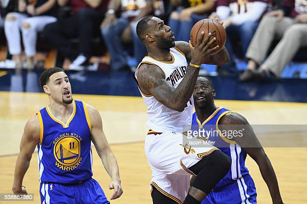 LeBron James of the Cleveland Cavaliers drives to the basket against Klay Thompson of the Golden State Warriors and Draymond Green during the first...