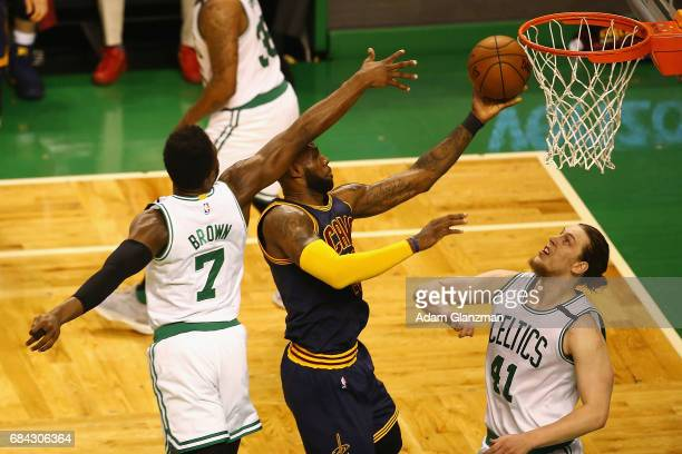 LeBron James of the Cleveland Cavaliers drives to the basket against Kelly Olynyk and Jaylen Brown of the Boston Celtics in the first half during...