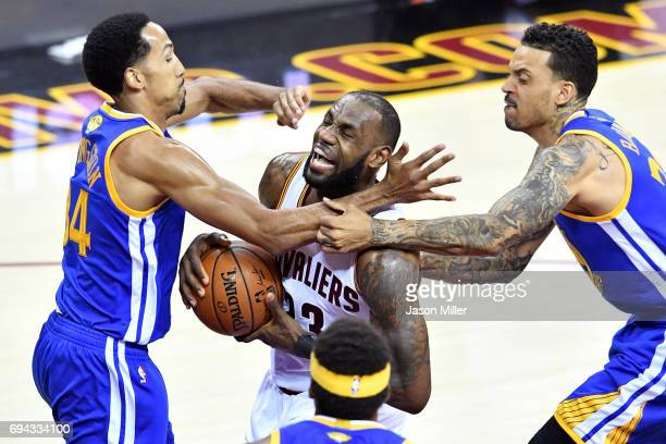 LeBron James of the Cleveland Cavaliers drives to the basket against Shaun Livingston and Matt Barnes of the Golden State Warriors in the first...