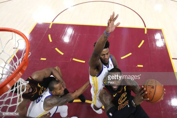 LeBron James of the Cleveland Cavaliers drives to the basket against Andre Iguodala and Jordan Bell of the Golden State Warriors in the first half...