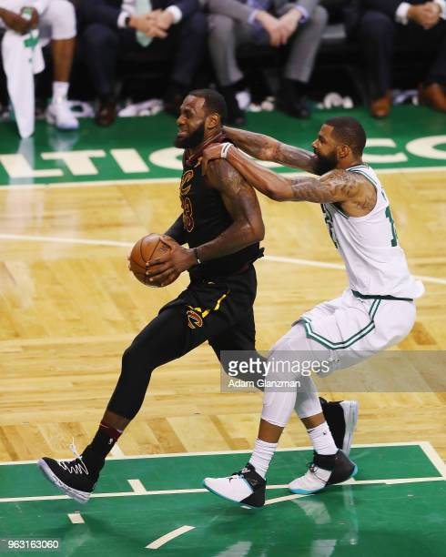 LeBron James of the Cleveland Cavaliers drives to the basket as he is fouled by Marcus Morris of the Boston Celtics in the second half during Game...