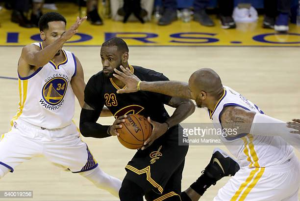 LeBron James of the Cleveland Cavaliers drives to the basket between Shaun Livingston and Marreese Speights of the Golden State Warriors in the...