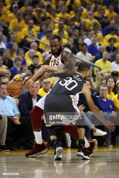 LeBron James of the Cleveland Cavaliers drives to the basket defended by Stephen Curry of the Golden State Warriors during the first quarter in Game...
