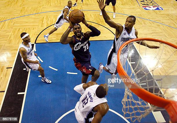 LeBron James of the Cleveland Cavaliers drives to the hoop against Dwight Howard and Rashard Lewis of the Orlando Magic in Game Six of the Eastern...