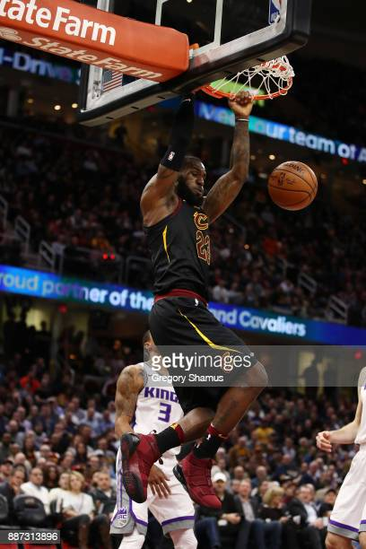 LeBron James of the Cleveland Cavaliers dunks in front of George Hill of the Sacramento Kings during the second half at Quicken Loans Arena on...
