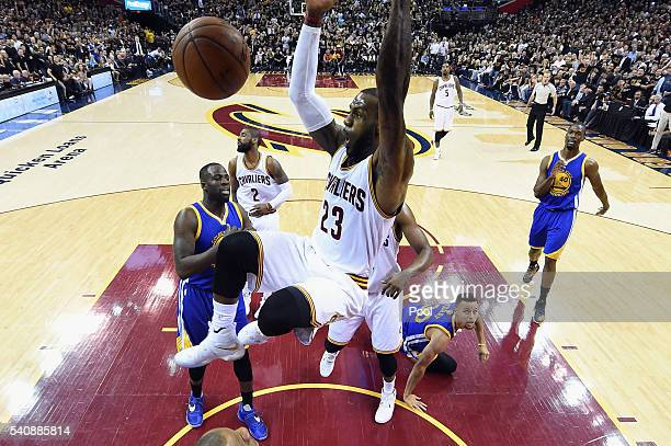 LeBron James of the Cleveland Cavaliers dunks in the first half against Draymond Green and Stephen Curry of the Golden State Warriors in Game 6 of...