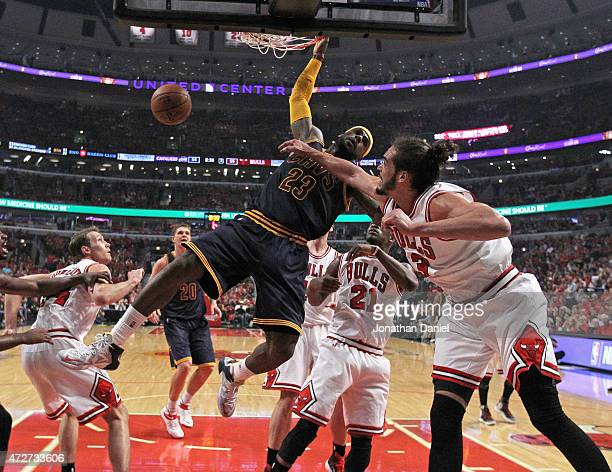 LeBron James of the Cleveland Cavaliers dunks over Mike Dunleavy Jimmy Buter and Joakim Noah of the Chicago Bulls in Game Three of the Eastern...