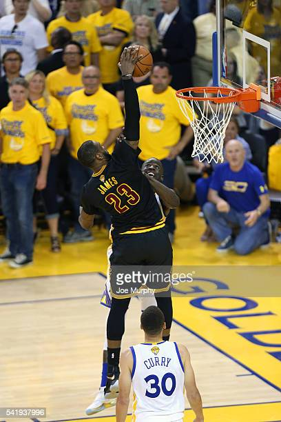 LeBron James of the Cleveland Cavaliers dunks the ball against Draymond Green of the Golden State Warriors during Game Seven of the 2016 NBA Finals...